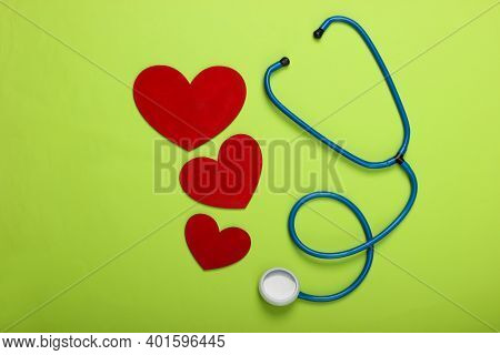 Stethoscope With Hearts On Green Background. Top View