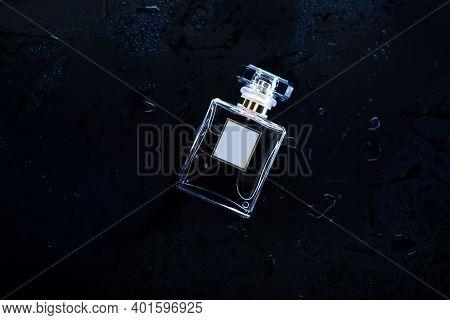 Female Perfume On A Wet Dark Background