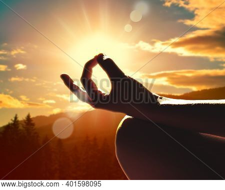 Close Up Of A Hand In A Meditation Pose. Sunset In The Mountains.