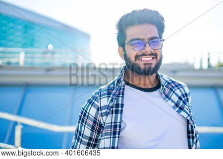 Arabian Young Man In Stylish Checkered Shirt And White T-shirt In Downtown At Summer Day