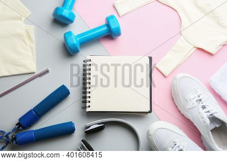 Flat Lay Composition With Sportswear, Notebook And Equipment On Color Background. Gym Workout Plan
