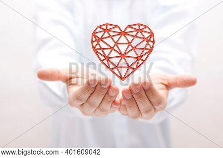 Red openwork heart in hands