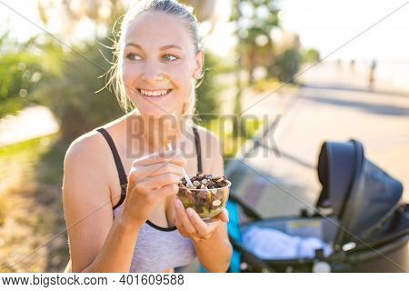Blonde Woman Holding Yoga Mat And Vegan Yogurt Ice Cream With Cocoa Bean Chocolate And Peanuts In Tr