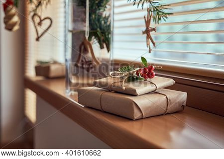 Christmas Presents Wrapped In Ecological Recycled Paper On A Windowsill, With Fir Branches And Straw