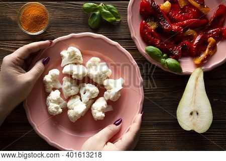 Cauliflower Healthy Snack On Rustic Wooden Table. Female Hands Holds Coral Living Plate. Natural Gri