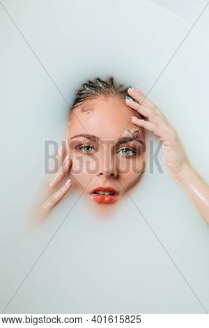 Beautiful Young Sexy Girl With Blonde Hair Wet, Exotic Makeup, Takes Bath With Milk Tan Perfect Skin