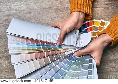 Color Wheel For Choosing Paint Tone. Hands Of Female Interior Designer Working With Palette For Choo