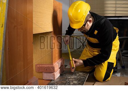 An Experienced Construction Worker, Wearing Protective Clothing And A Helmet, Measures The Decorativ