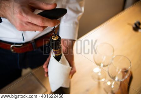 Uncorking Bottle Of Wine With A Wine Opener. Wine Tasting With A Sommelier.