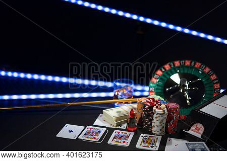 Casino set with Roulette, cards, dice and chips on Black table mat Shallow depth of field