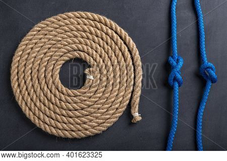 A Rope Coiled In A Circle And Two Sailing Knots. Accessories For Sea Wolves On The Table.