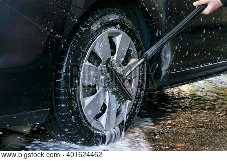 Car Wash Outdoor. Washing Car Wheel With A Washing Brush, Close Up.