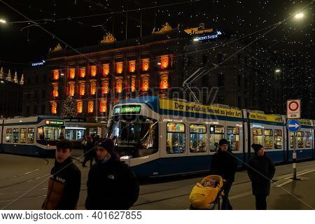 Paradeplatz At Christmastime At Night. Illuminated Windows Of Headquarter Of Banks And Tram Station
