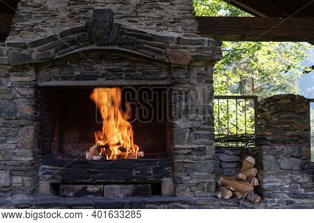 Nice fireplace in the garden red flames in stone.  Place to relax, cook