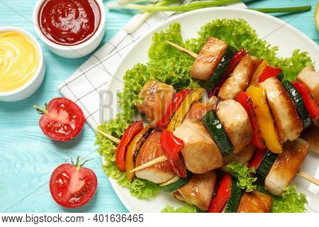 Delicious Chicken Shish Kebabs With Vegetables And Sauce On Light Blue Wooden Table, Closeup