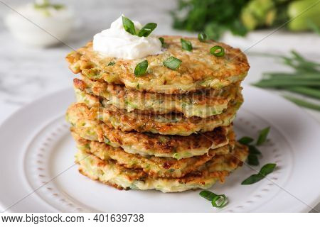 Delicious Zucchini Fritters With Sour Cream And Green Onion On Plate, Closeup