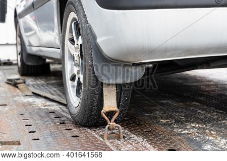 Close-up Of Car Wheel Tied With Safety Harness On Flatbed Tow Truck