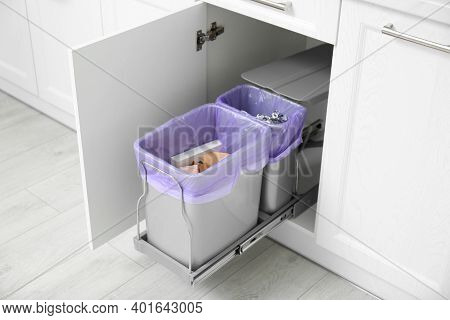 Open Cabinet With Full Trash Bins For Separate Waste Collection In Kitchen