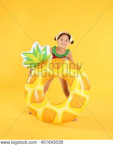 Cute Little Child In Beachwear With Bright Inflatable Ring On Yellow Background