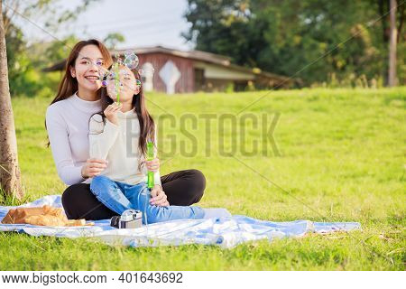 Happy Family Picnic. A Little Girl Blowing Soap Bubbles With Parents (father, Mother) With Fun And E