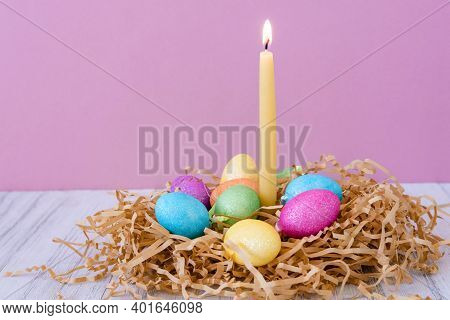 Easter Card With Nest, Colored Eggs And Burning Wax Candle On Purple  Pastel Background. Spring And
