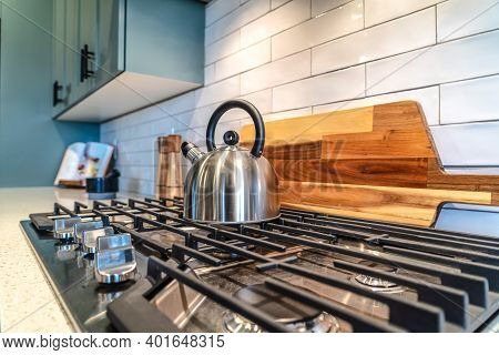 Home Kitchen Interior With Kettle Over The Burner Of A Cooktop With Five Knobs