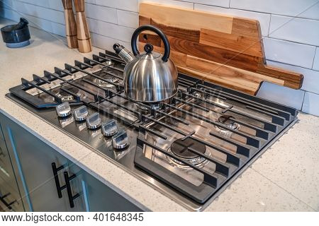 Kettle On Top Of A Cooktop Against Wooden Chopping Board And Tile Backsplash