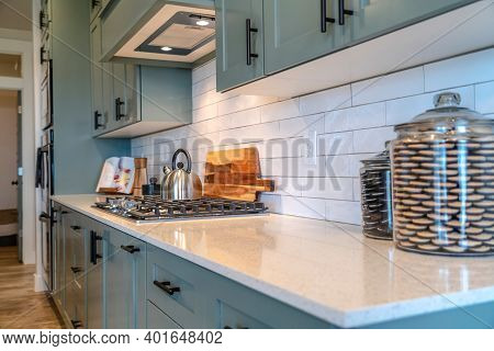 Kettle On Cooktop Fixed On White Countertop With Cookie Jars Inside Home Kitchen