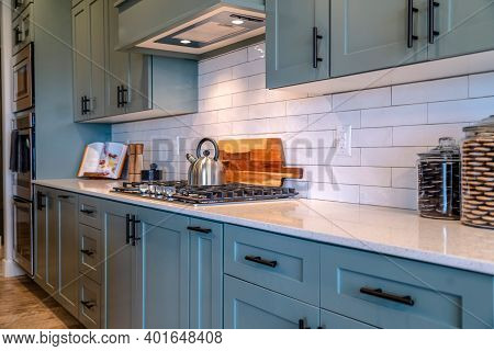 Cooking Area Of Home With Cabinets And Exhaust Hood Over Cooktop And Countertop