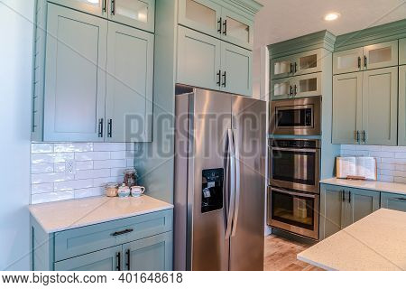 Modern Electric Cooking Appliances And Built In Cabinets Inside Kitchen Of Home