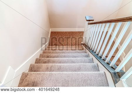 Interior Stairway With U Shaped Design Carpet On Treads And Wooden Handrail