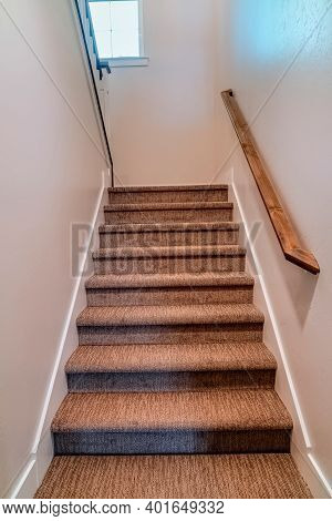 Stairway Inside Home With Wall Mounted Wooden Handrail And Carpet On The Treads