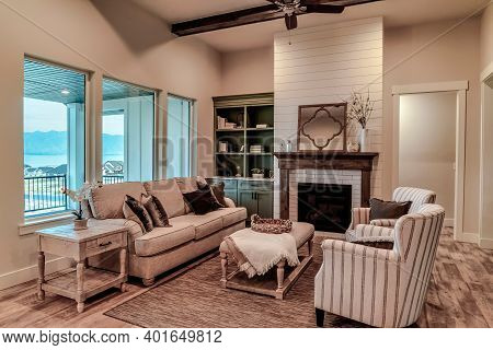 Living Area Of Home With Upholstered Funiture Modern Fireplace And Ceiling Fan