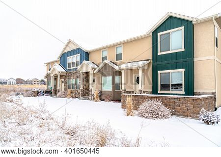 Two Storey Apartment With Gabled Entrances On A Snowy Neighborhood In Winter