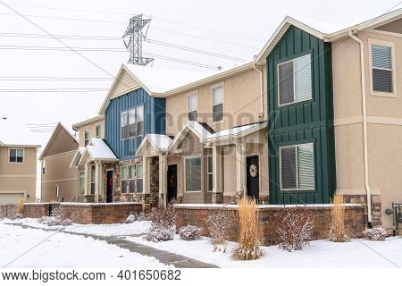 Pathway On Snowy Yard In Front Of Apartments With Porches And Gabled Entrances