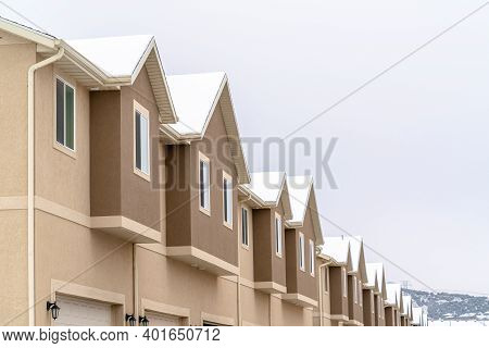 Focus On Upper Floors Of Two Storey Townhouses Against White Sky View In Winter