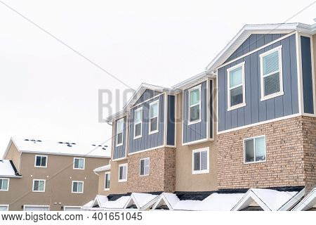 Upper Floors Of Apartments And Townhouses Against Snow And Cloudy Sky In Winter