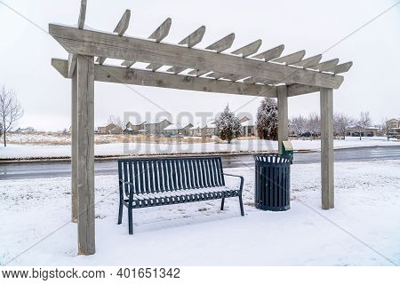 Wooden Pergola Over Bench And Garbage Can Along A Road On A Snowy Winter Day