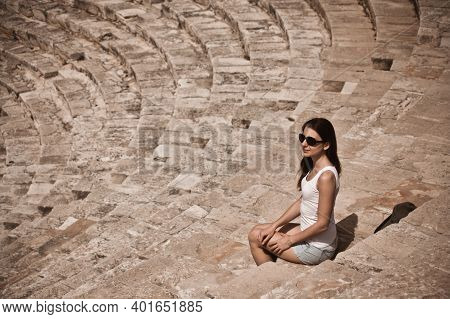 Young Woman Sitting In Ancient Odeon Amphitheatre In Paphos Archaeological Park. Portrait Of Girl Po