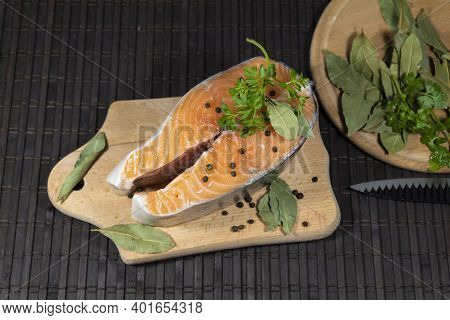 A Piece Of Red Salmon Fish Lies On A Cutting Board. On Top Are Peppercorns, Parsley And Bay Leaves.
