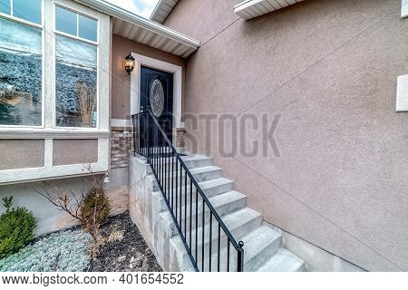 Outdoor Stairs With Handrail And Front Door With Oval Glass Pane At Home Facade