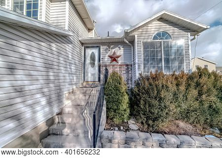 Home With Gray Wall Siding And Stairs At Front Entrance With Glass Paned Door