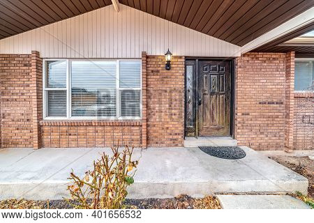 Font Of Brick Home With Glass Paned Front Door And Transom Window At Entrance