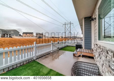 Back Yard Of Townhouse With Grassy Lawn Inside Low Wooden Picket Fence And Gate