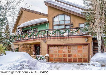 Home With Snowy Yard And Driveway In Front Of Front Door And Metal Garage Door