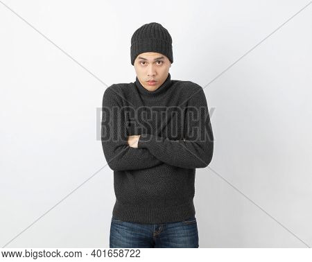 Young Handsome Asian Man Wearing Grey Sweater And Beanie Hugging Herself And Trembling, Shaking From