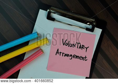 Voluntary Arrangement Write On Sticky Notes Isolated On Wooden Table. Business Or Finance Concept