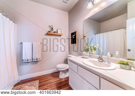 Toilet Beside Vanity Unit With Sink Mirror And White Cabinets Inside Bathroom