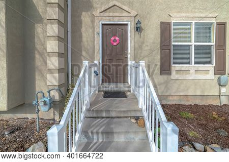 Concrete Stairs With Handrails At The Entrance Of House With Brown Front Door