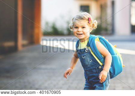 Cute Little Adorable Toddler Girl On Her First Day Going To Playschool. Healthy Beautiful Baby Walki